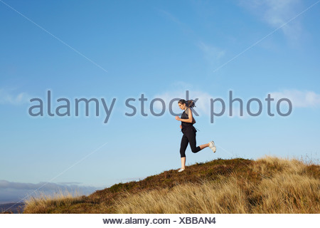 Woman running on rural hillside - Stock Photo