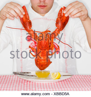Man dining with an entire lobster - Stock Photo