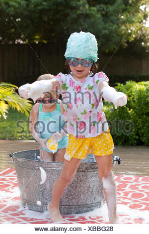 Girl and toddler sister playing in bubble bath in garden - Stock Photo