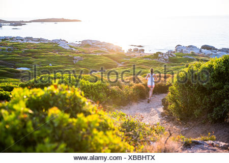Young Woman running along a trail, Corsica, France - Stock Photo
