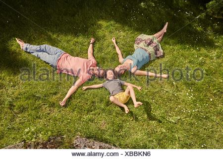 Mother, father and son, in garden, lying on grass, relaxing - Stock Photo