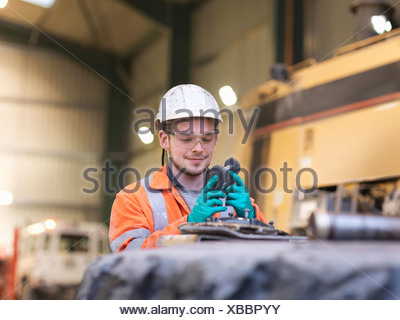 Apprentice engineer inspecting equipment in surface coal mine - Stock Photo
