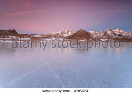 The snowy peaks are reflected on the frozen surface of Andossi Lake at dawn Spluga Valley Valtellina Lombardy Italy Europe - Stock Photo