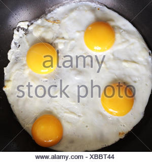London, UK Four Eggs Frying In A Pan - Stock Photo