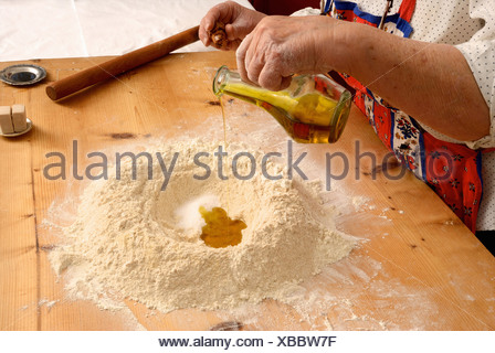Older woman baking on wooden board - Stock Photo