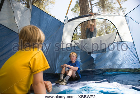 Two young boys sitting in an empty tent - Stock Photo