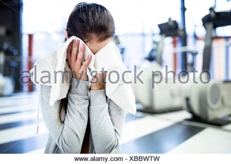 PROPERTY RELEASED. MODEL RELEASED. Cute young woman wiping her sweat after workout in gym. - Stock Photo