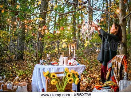 Mature woman hanging decorative lights in woods - Stock Photo