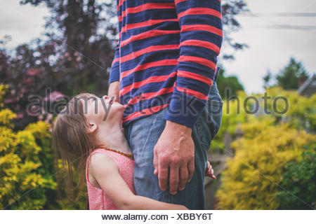 Daughter holding father's legs, looking up - Stock Photo