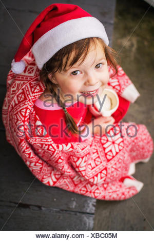 Girl wrapped in festive blanket holding a mug of  hot cocoa - Stock Photo