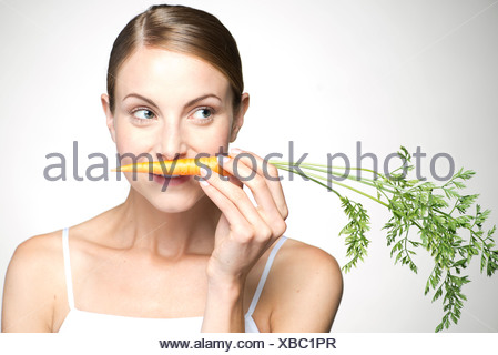 Young woman smelling carrot - Stock Photo