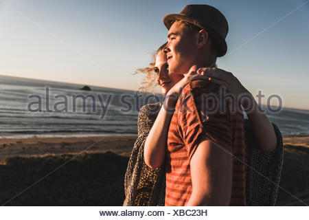 Young couple in love watching sunset on the beach - Stock Photo