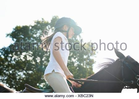 Cropped view of girl riding horse in countryside - Stock Photo