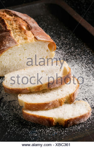 Sliced homemade white wheat bread with wheat flour on old black oven tray as background. Close up - Stock Photo