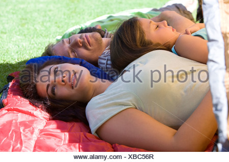 Family lying on sleeping bags in tent entrance on garden lawn father and children 7 9 sleeping mother daydreaming side view - Stock Photo