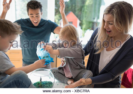 Young family feeding goldfish in bowl - Stock Photo