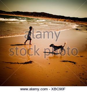 A boy and a dog on a beach having fun - Stock Photo