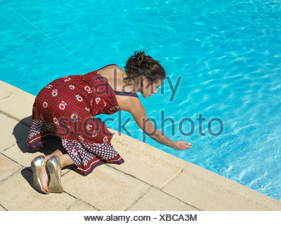 Girl testing pool water - Stock Photo