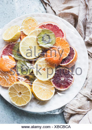 Overhead view of sliced citrus fruits served and covered on plate - Stock Photo