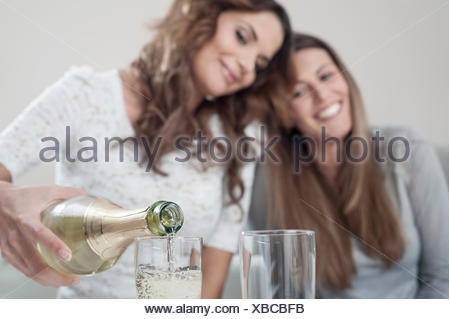 Young woman pouring champage into glasses while her female friend watching - Stock Photo