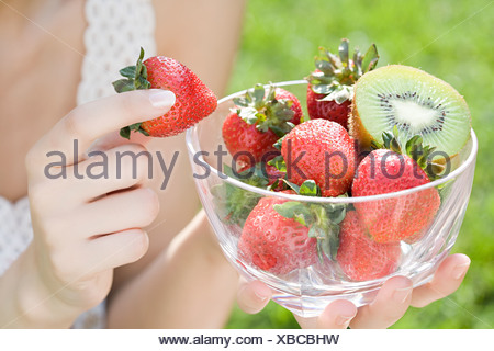 Woman with bowl of strawberries and kiwi - Stock Photo