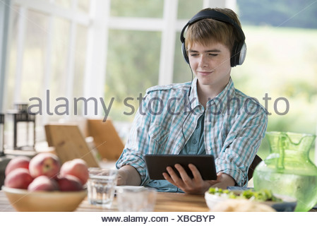 A young boy listening to music and using a digital tablet.