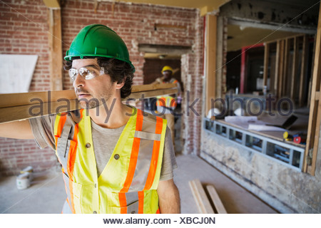 Tradesmen carrying lumber at construction site - Stock Photo
