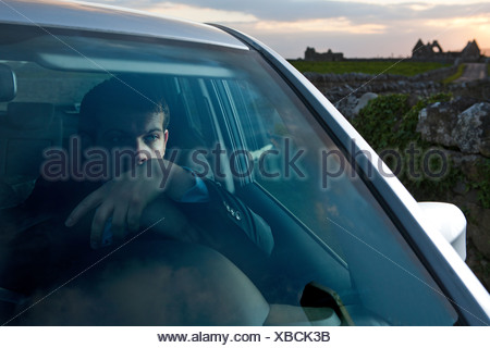 Businessman leaning on steering wheel in car - Stock Photo