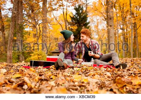Happy young couple having picnic in autumn forest - Stock Photo
