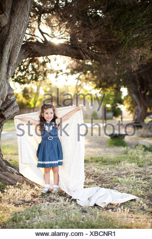 Portrait of girl holding sheet with arms out under tree - Stock Photo