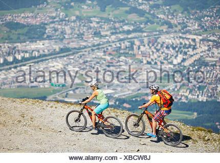 Man 40-45 years and woman 35-40 years with helmets cycle with their mountain bikes, Zirbenweg, Patscherkofel, Innsbruck, Tyrol - Stock Photo