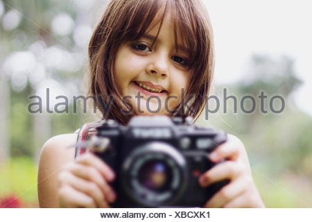 Portrait Of A Smiling Girl Holding Camera Outdoors - Stock Photo