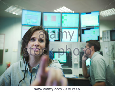 Scientists in accelerator control room - Stock Photo