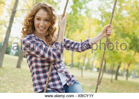 Happy mid adult woman swinging at park - Stock Photo