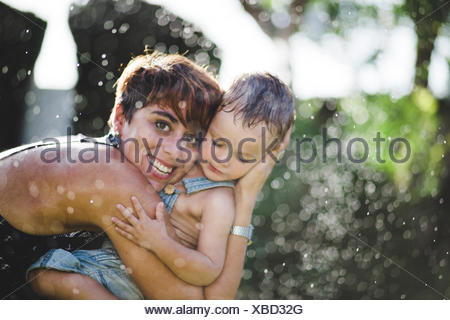 Lttle boy and his mother enjoying splashing water in the garden - Stock Photo