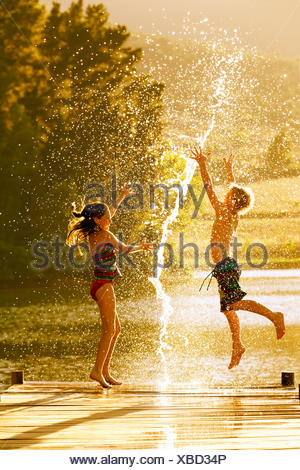 Young boy and girl jumping in air on jetty through splash of water - Stock Photo