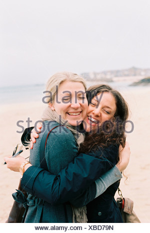 Two women cheek to cheek hugging on a beach. - Stock Photo