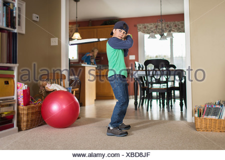 Portrait of boy practicing baseball in sitting room - Stock Photo