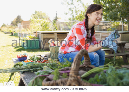 Cheerful woman sitting in community garden - Stock Photo