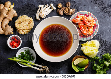 Raw ingredients for asian spicy Ramen noodles with Prawns  around bowl of broth - Stock Photo