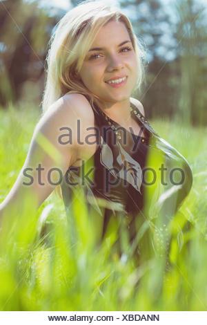 Pretty blonde in sundress sitting on grass - Stock Photo