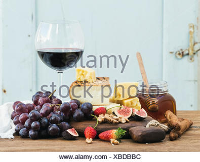 Glass of red wine, cheese board, grapes,fig, strawberries, honey and bread sticks  on rustic wooden table, blue background, sele - Stock Photo