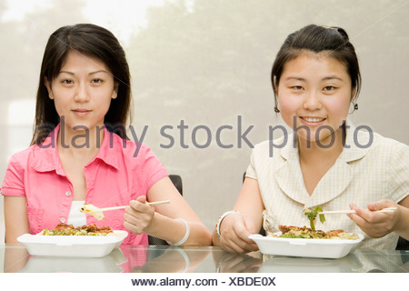 Portrait of two female office workers having lunch - Stock Photo