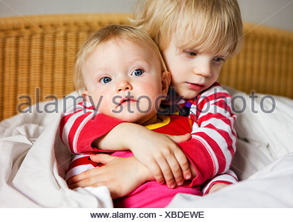 Boy embracing sister on bed - Stock Photo