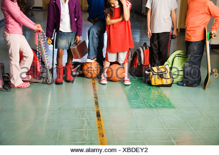 Group of students with sports equipment in hallway - Stock Photo