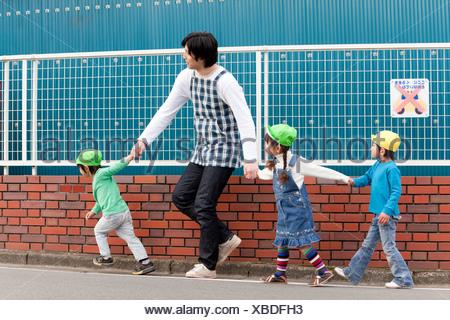 Nursery Teacher and Children Walking - Stock Photo