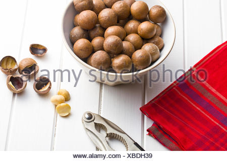 macadamia nuts in bowl on white wooden table - Stock Photo