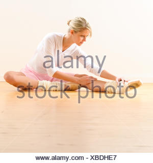 Beautiful ballet dancer stretching in the studio - Stock Photo