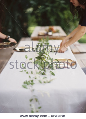 Two people leaning over a table laid outside with a white cloth and a central foliage table decoration - Stock Photo