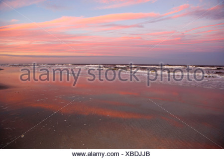 View from sandy beach of picturesque red sunset horizon over sea - Stock Photo